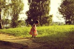 portrait de vintage de promenade mignonne de petite fille sur un champ d'été Images libres de droits