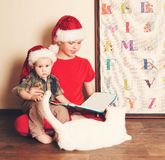 Portrait de vintage des garçons dans des chapeaux de Santa lisant un livre de Noël Photos stock