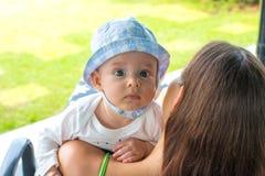 Portrait de visage de bébé avec l'expression curieuse et yeux bleus focalisés au-dessus des épaules aimantes de mère image libre de droits