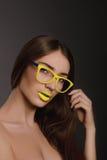 Portrait de visage de femme de beauté avec les lèvres jaunes et les verres jaunes Photographie stock