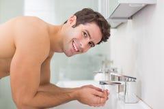 Portrait de visage de lavage d'homme sans chemise dans la salle de bains Images libres de droits