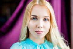 Portrait de visage de femme de beauté Fille modèle portant la robe bleue posant à l'arrière-plan de pourpre de studio de lumière  image stock