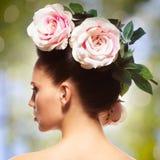 Portrait de vue arrière de la femme avec les fleurs roses dans des poils Image libre de droits