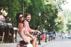 Portrait de vue arrière des couples heureux montant un scooter Images libres de droits