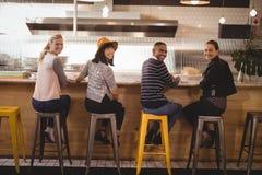 Portrait de vue arrière de jeunes amis de sourire s'asseyant sur des tabourets au compteur Image stock