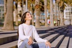 Portrait de vue de côté d'une détente de jeune femme images stock