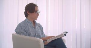 Portrait de vue de côté de plan rapproché du jeune homme d'affaires caucasien bel lisant un livre se reposant dans le fauteuil à  banque de vidéos