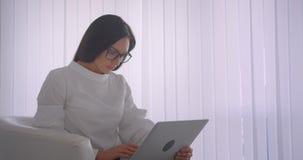 Portrait de vue de côté de plan rapproché de jeune jolie femme d'affaires caucasienne en verres utilisant l'ordinateur portable r clips vidéos