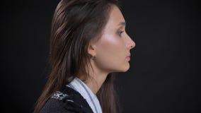 Portrait de vue de côté de plan rapproché de jeune visage femelle caucasien mignon avec des cheveux de brune regardant en avant a photos libres de droits
