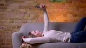Portrait de vue de côté de plan rapproché de la jeune femelle caucasienne attirante de brune prenant des selfies sur le mensonge  banque de vidéos