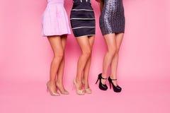Portrait de vue de côté de trois belles filles dans la robe montrant leurs jambes douces sur le fond rose Photographie stock libre de droits