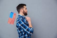 Portrait de vue de côté d'un homme occasionnel tenant le drapeau des Etats-Unis Photo stock