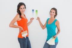 Portrait de vue de côté de deux amis féminins choisissant la couleur Photo stock