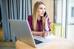 Portrait de vue de côté de la jeune femme d'affaires ayant l'appel d'affaires dans le bureau, son lieu de travail, notant de l'in Image libre de droits
