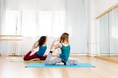 Portrait de vue de côté de pose de pigeon de pratique en matière de deux jeunes femmes Image stock