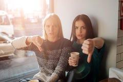 Portrait de vue de face de deux amis drôles avec des pouces vers le bas et regardant à l'appareil-photo Images stock