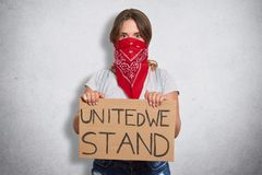 Portrait of decisive young woman paying attention to feminism problem, believing in equal rights, looking for support, holding. Sign united we stand in both royalty free stock image