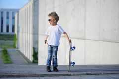 A portrait of defiant boy with skateboard outdoors. royalty free stock image