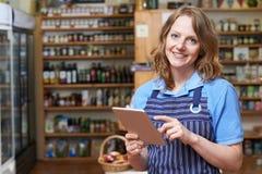 Portrait Of Delicatessen Owner With Digital Tablet. Delicatessen Owner With Digital Tablet stock image