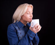 Portrait of delighful girl with cup. Attractive blond girl holding cup of hot coffee Stock Images