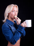 Portrait of delighful girl with cup and cookie. Attractive blond girl eating cookie and drinking coffee Royalty Free Stock Photography