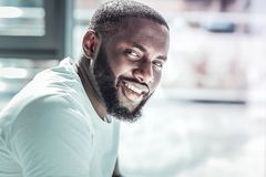 Portrait of delighted Afro-American that posing on camera. Deep in thoughts. Handsome male person keeping smile on his face and turning head while looking royalty free stock photo