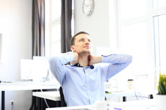 Portrait of a delighted businessman relaxing in his office. Royalty Free Stock Image