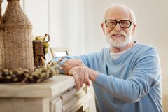 Portrait of delighted senior male that posing on camera. Just pose. Cheerful man keeping smile on his face and holding hands together while looking forward Royalty Free Stock Photo