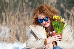 Portrait of delighted stylish woman resting in snow and looking down through blue sunglasses royalty free stock photos