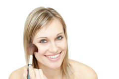 Portrait of a delighted woman using a powder brush Royalty Free Stock Photos