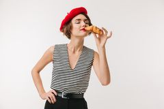 Portrait of a delighted woman wearing red beret. Smelling croissant isolated over white background Stock Images