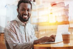 Portrait of delighted worker that posing on camera. Facial expressions. Cheerful brunette keeping smile on his face and turning head, using computer Royalty Free Stock Image