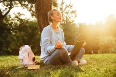 Portrait of a delighted young girl in earphones. With backpack sitting with legs crossed on a grass at the park, using laptop computer Royalty Free Stock Photo