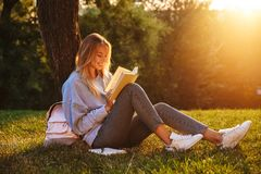 Portrait of a delighted young girl sitting on a grass. At the park, reading a book, taking notes Stock Image
