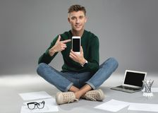 Pleased guy making demonstration of his devices. Portrait of delighted young person with smartwatch on hand pointing at mobile phone. Laptop and stationery are Royalty Free Stock Image