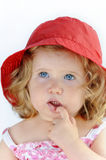 Portrait of delightful baby girl with red hat. Baby girl,  nearly two years old in a pink dress and red hat with her finger in her mouth showing her teeth. Low Stock Photo