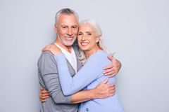 Portrait of delightful tender gentle elderly spouses who are rel. Axing, hugging, they have perfect ideal beaming shiny smiles, isolated on grey background Royalty Free Stock Images
