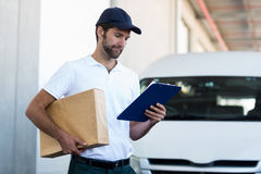 Portrait of delivery man is holding a cardboard box and looking a clipboard Royalty Free Stock Photos