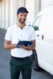 Portrait of delivery man holding a clipboard next to his van Royalty Free Stock Images