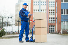Portrait Of Delivery Man With Parcels And Clipboard Stock Photo