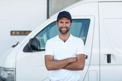 Portrait of delivery man is posing with crossed arms. In front of a warehouse Royalty Free Stock Photography