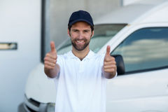 Portrait of delivery man showing thumbs up Stock Photos