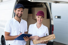 Portrait of delivery man and woman standing with clipboard and parcel Stock Photos