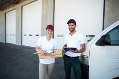 Portrait of delivery man and woman standing with clipboard and parcel Stock Photography