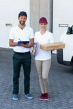 Portrait of delivery man and woman standing with clipboard and parcel Royalty Free Stock Photos