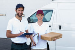 Portrait of delivery man and woman standing with clipboard and parcel Stock Photo
