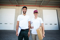 Portrait of delivery man and woman standing with clipboard and parcel Royalty Free Stock Photography