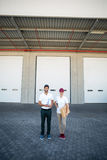 Portrait of delivery man and woman standing with clipboard and parcel Royalty Free Stock Image