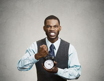 Portrait of demanding corporate boss holding alarm clock screami Royalty Free Stock Photography