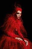 Portrait of a demonic woman in a luxury red dress. Studio shot on a dark background Stock Photos